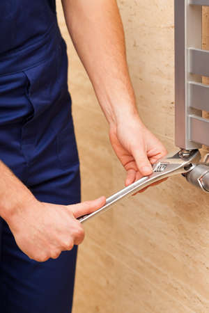 Handyman repairing heater with a metal wrench photo