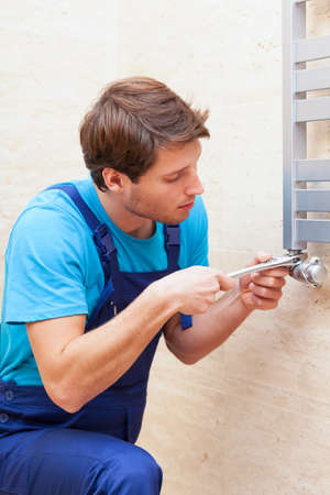 Young repairman fixing heater with special tool