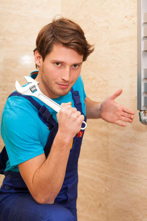 Strong handsome handyman repairing radiator with wrench photo