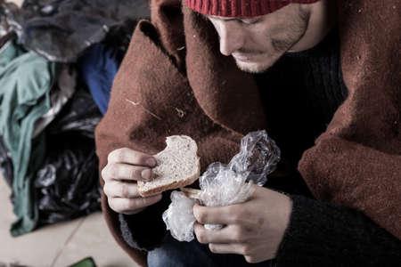 hombre pobre: Pobre hombre que come el emparedado en la calle Foto de archivo