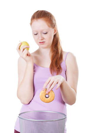 Redhead girl choosing apple instead of a doughnut photo