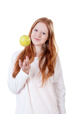 Redhead girl tossing an apple on isolated white background photo