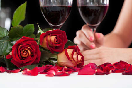 Close up of beautiful red roses and glasses with wine