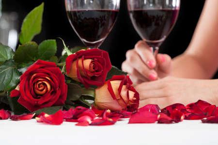 Close-up van mooie rode rozen en glazen met wijn Stockfoto