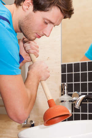 Handyman using plunger for washbasin in bathroom photo
