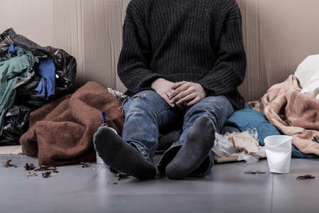 Homeless man sitting on the street, horizontal