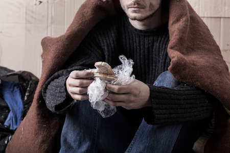 Homeless man eating sandwich on the street photo