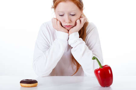 Young girl choosing between doughnut and red peppers photo