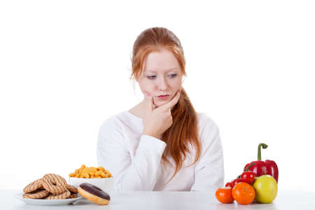 whether: Teenage girl wondering whether to eat sweets or vegetables
