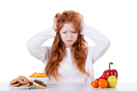 what to eat: Confused girl trying to decide what to eat Stock Photo