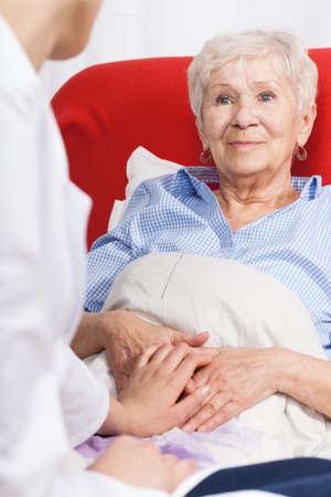 Nurse visiting recovering senior patient at home photo