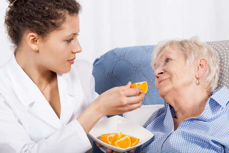 Nurse feeding an elderly woman at home photo