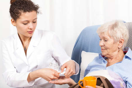 Home nurse giving elderly woman vitamin pills