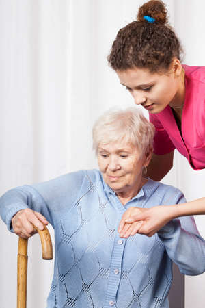 get help: Nurse helping elderly woman get up, vertical Stock Photo