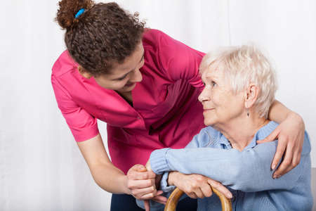 Beautiful nurse taking care of senior woman