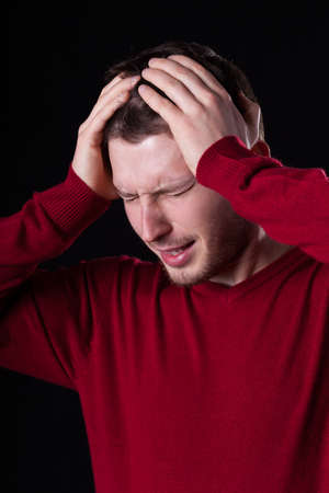 throe: Man suffering from headache on isolated background