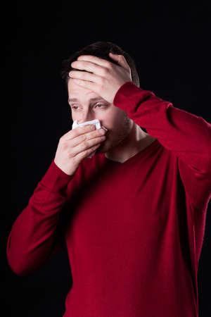 catarrh: Young man suffering from running nose, vertical