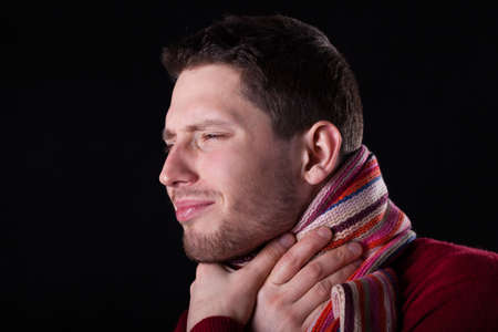 throe: Man suffering from sore throat on isolated background Stock Photo