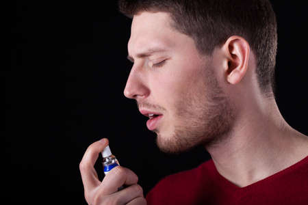 throe: Man applying spray for sore throat, horizontal