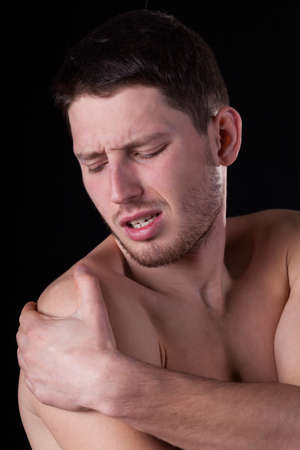 throe: Man having arm pain on isolated background Stock Photo