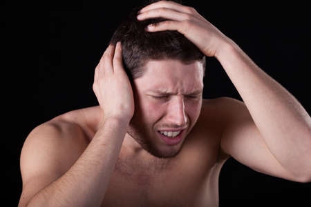 throe: Man feeling headache on isolated black background