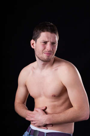 diarrhoea: Handsome man with stomach ache on isolated background Stock Photo