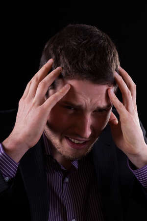 throe: Businessman feeling migraine on isolated black background