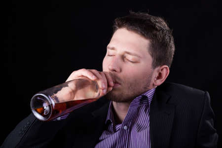 Horizontal view of a drunk businessman drinking wine photo