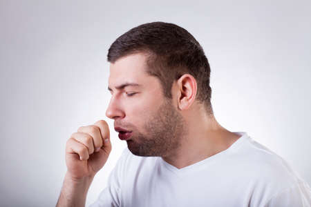 Close-up of a young man having a cough photo