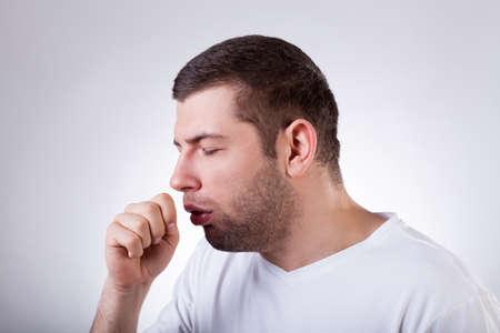 cough: Primer plano de un hombre joven que tiene una tos