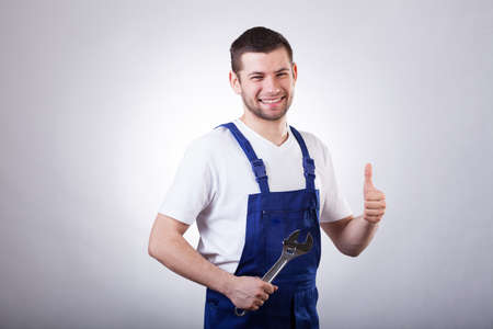 Handsome repairman showing ok gesture and holding spanner photo