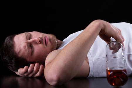 alcoholic man: Drunk man lying on the floor, horizontal Stock Photo