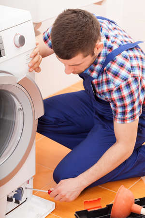 Young repairman fixing broken washing machine, vertical