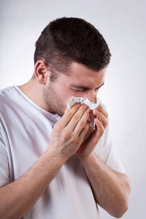 catarrh: Sick young man with running nose, vertical Stock Photo