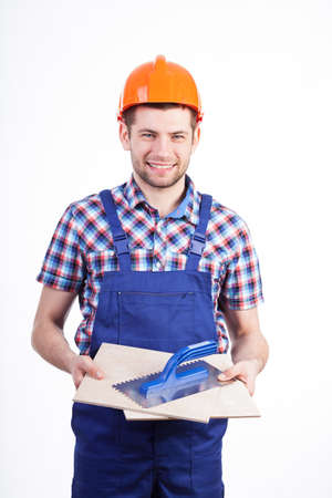 grout: Portrait of a young male tiler with ceramic tiles and grout float Stock Photo
