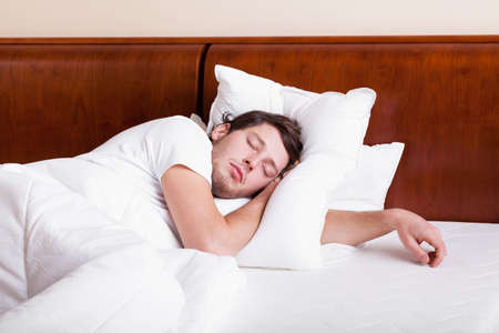 bedlinen: Young man sleeping alone in white bedclothes