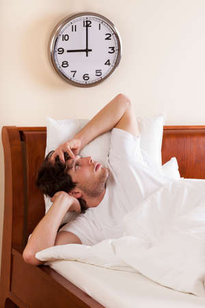 Young man waking up with morning headache photo