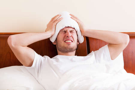 Young man suffering from headache lying in bed photo