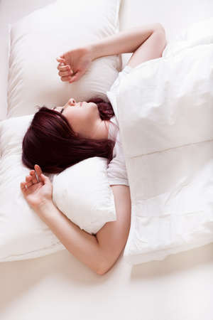 bedlinen: Young beautiful woman sleeping alone in bed Stock Photo