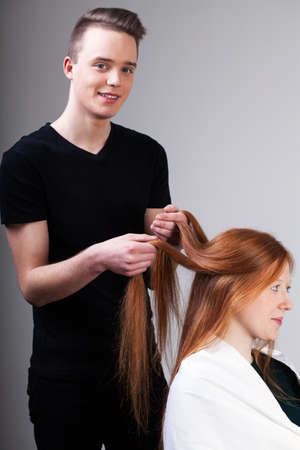 man long hair: Male hairdresser is combing female customer hair