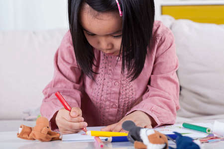 Concentrated girl drawing a picture with crayons photo