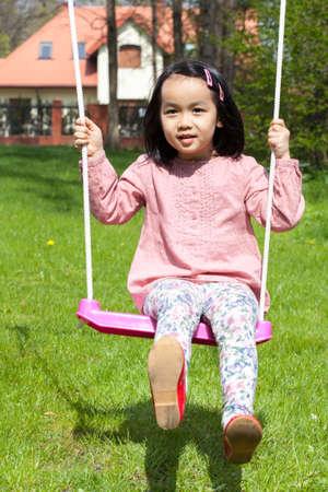 asian family outdoor: Asian girl swinging in a garden, vertical Stock Photo