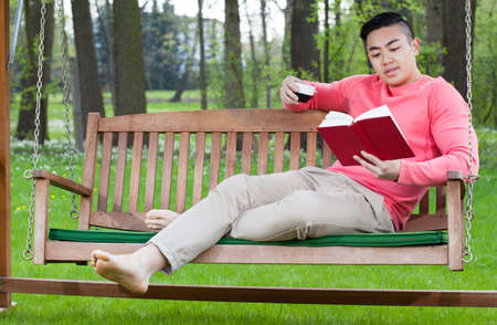 Asian man relaxing with book and coffee photo