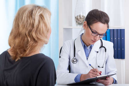 Female doctor making notes during conversation with patient, horizontal photo