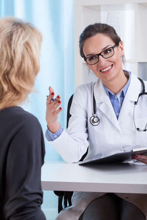 Young female internist talking and smiling to patient photo
