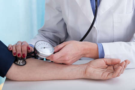 doctor examining woman: Close-up of measuring blood pressure, horizontal view Stock Photo