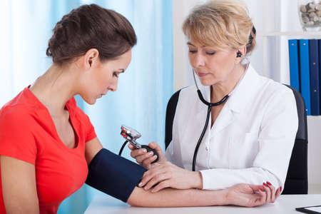 Arts die de bloeddruk van de vrouwelijke patiënt op kantoor