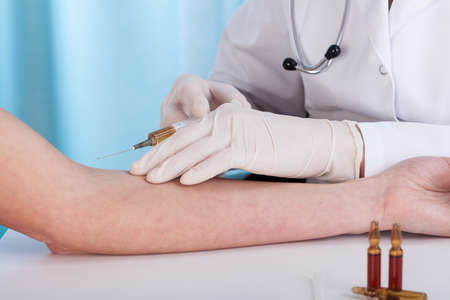 surgical needle: Close-up of hands giving vaccination injection and ampoules, horizontal