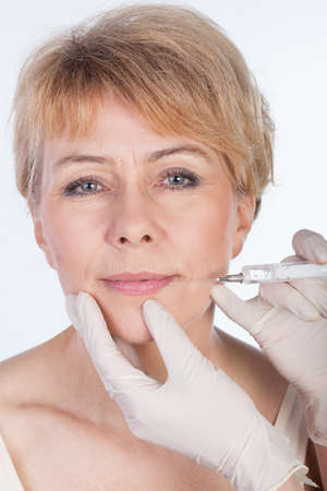 Middle aged woman receiving a botox injection in her lips