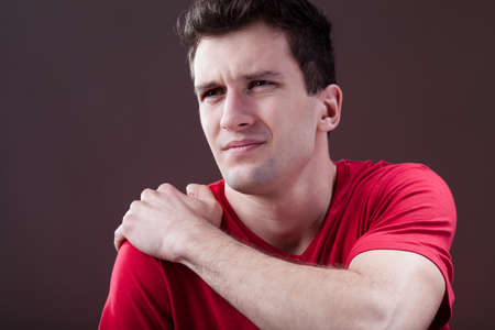 arm pain: A handsome man suffering form a painful shoulder